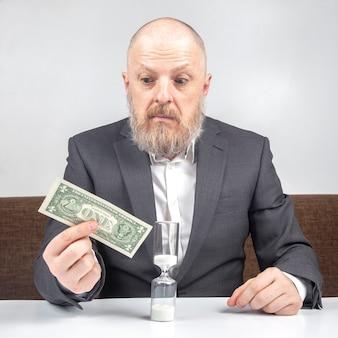 수염 된 사업가 모래 시계의 배경에 대해 돈으로 작업에 대한 지불을 제공합니다. 비즈니스 비용을 지불하는 시간의 가치 개념.