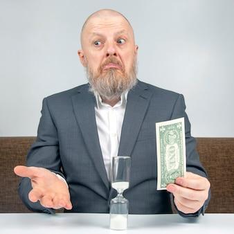 ひげを生やしたビジネスマンは、砂時計に対してお金で仕事の支払いを提供します。ビジネスに支払う時間の価値の概念。