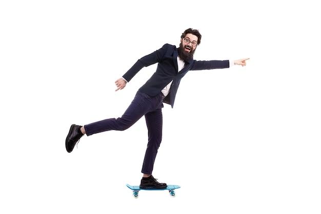 白い背景で隔離のスケートボードに乗ってひげを生やした実業家