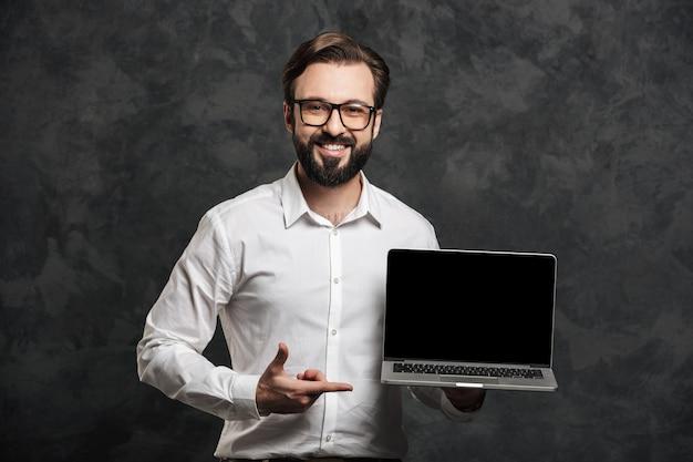 Бородатый бизнесмен показывает дисплей ноутбука