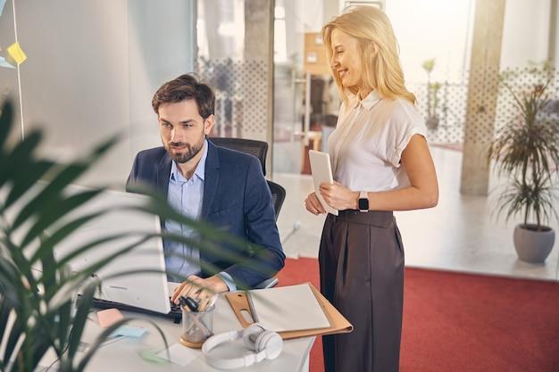 Бородатый бизнесмен сидит за столом и использует компьютер, улыбаясь коллеге, стоящей рядом с ним