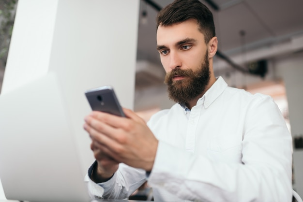 Bearded businessman using laptop and smartphone