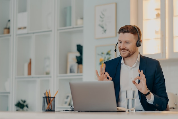 Бородатый бизнесмен очень доволен результатом онлайн-переговоров при использовании ноутбука и гарнитуры, счастливый офисный работник мужского пола показывает знак ок обеими руками и улыбается. концепция бизнеса и работы