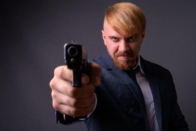 Бородатый бизнесмен с пистолетом на сером