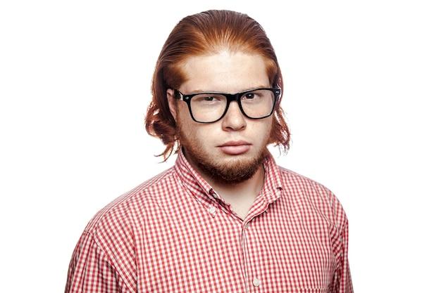빨간 셔츠와 안경을 쓴 수염난 사업가가 카메라를 쳐다보고 있다
