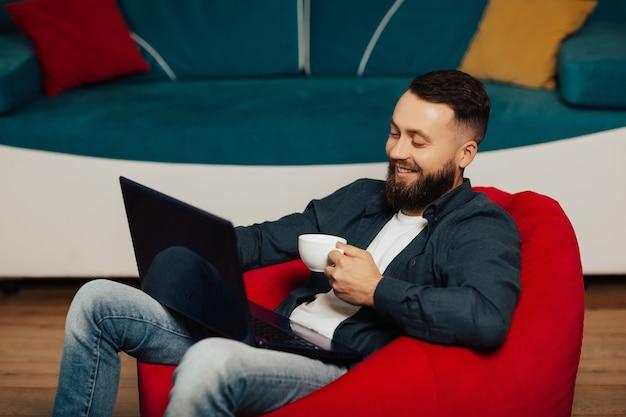 自宅でラップトップに取り組んでいるひげを生やしたビジネスマンとコーヒーブレイク。ラップトップコンピューターと赤い肘掛け椅子に座って、リビングルームでコーヒーを飲む幸せな男。