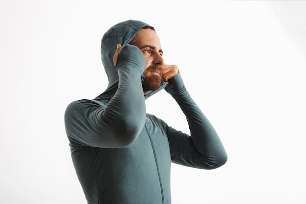 Atleta caucasico barbuto si adatta alla felpa con cappuccio della sua tuta termica in lana merino wither snowboard baselayer