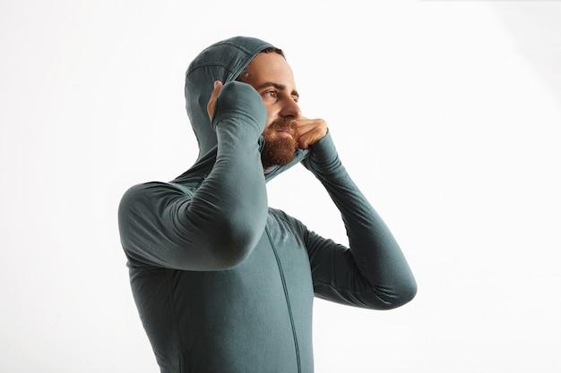 Бородатый спортсмен-европеоид подходит к худи из своего комплекта термобелья из шерсти мериноса.