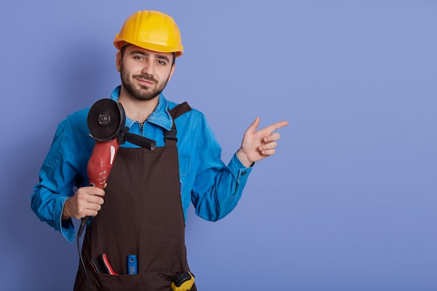 Bearded caucasian builder with grinder in hands posing isolated over blue background and pointing index finger aside at copy space