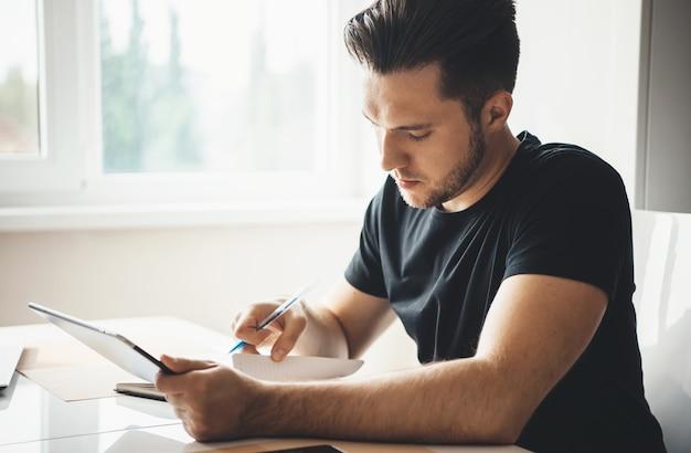 タブレットとリビングルームで黒いtシャツを着ていくつかの紙を使用して自宅で仕事をしているひげを生やした白人ビジネスマン