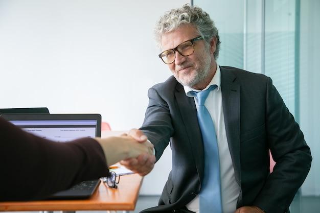 Handshaking e sorridente del responsabile esecutivo caucasico barbuto
