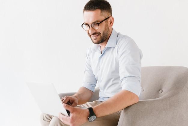ひげを生やした白人男の肘掛け椅子に座っていると白で隔離のラップトップに取り組んでスタイリッシュなフォーマルな服を着ています。