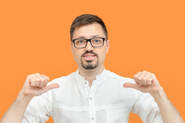 Bearded caucasian man in eyeglasses indicating himself with fingers. handsome guy looking confident with smile on face pointing oneself with proud and happy isolated on yellow color background.