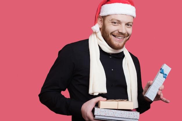 ひげを生やした白人男性がカメラでサンタの帽子と黒い服を着て空きスペースのある赤い壁に微笑んでいるいくつかのプレゼントを見せています