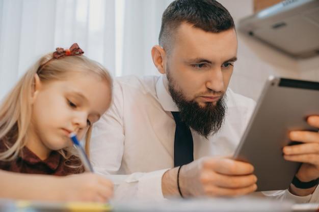 Бородатый кавказский мужчина смотрит на свой планшет, стоящий рядом с дочерью, пока она что-то рисует