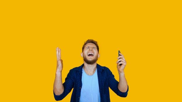 電話を使用しているひげを生やした白人男性が何かを獲得した後に身振りで示す