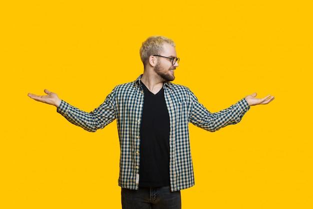 금발 머리를 가진 수염 난 백인 남자가 노란색 벽에 포즈를 취하는 동안 손바닥에서 두 가지를 비교하고 있습니다.