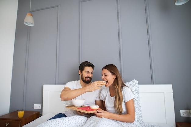 Бородатый жизнерадостный мужчина дает красивой молодой девушке завтрак в постели. Premium Фотографии