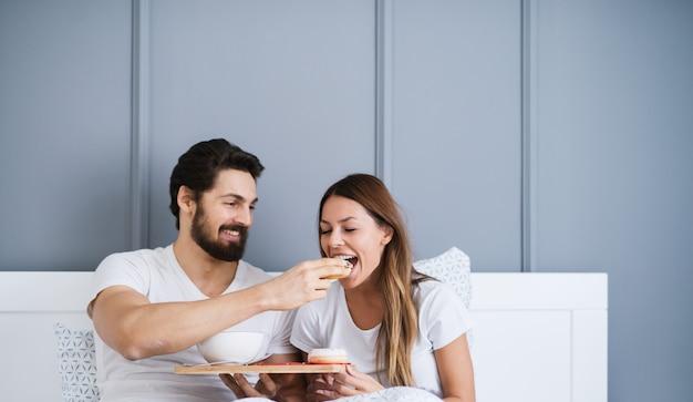 Бородатый жизнерадостный мужчина дает красивой молодой девушке завтрак в постели.