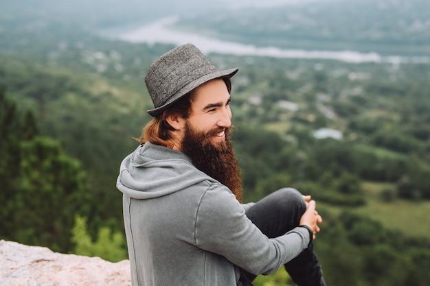 ひげを生やした、陽気な観光客は夏の美しい風景を見ています。