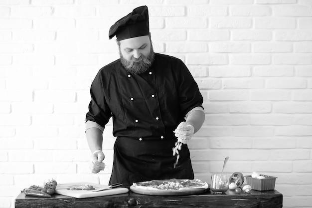 ひげを生やしたシェフシェフがキッチンのテーブルで食事を準備します