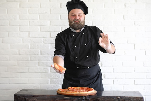 Bearded chef chef prepares meals at the table in the kitchen
