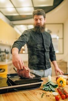 Бородатый повар готовит мясо на сковороде на кухне. человек готовит вареную свинину на электрической плите стола
