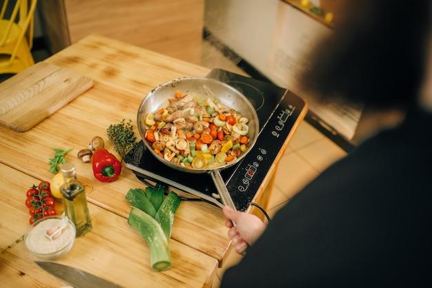 Бородатый повар готовит мясо с овощами на сковороде на кухне.