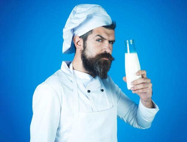 Бородатый шеф-повар в униформе с бутылкой молока. напитки, молочные фермерские продукты, диета.