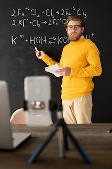 Bearded chemistry teacher in casualwear pointing at chemical formula on blackboard while looking at smartphone camera during online lesson