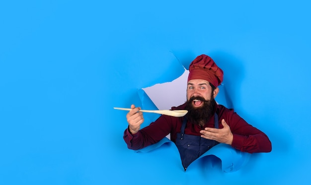 Bearded cook holds wooden kitchen cooking tools looking through paper bearded man chef cook with