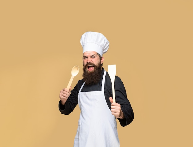 Bearded cook with wooden spoon and spatula in hand cooking bearded man preparing to cook food