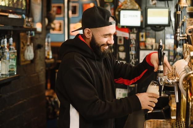 Бородатый мужественный мужчина наливает вам пенный напиток