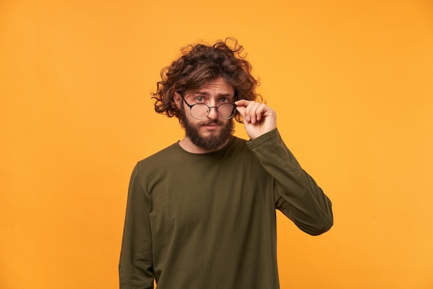 Bearded curly-headed man looked something curious and takes off his glasses