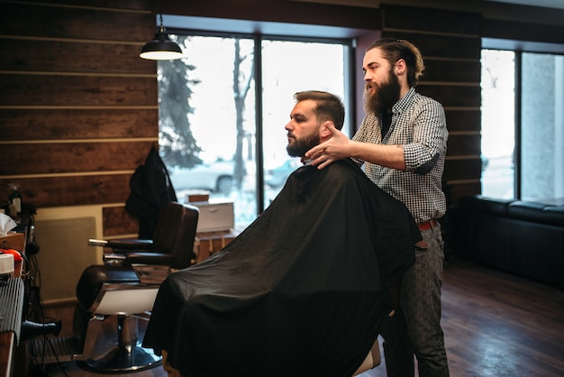 Bearded customer man in black salon cape visit barbershop.