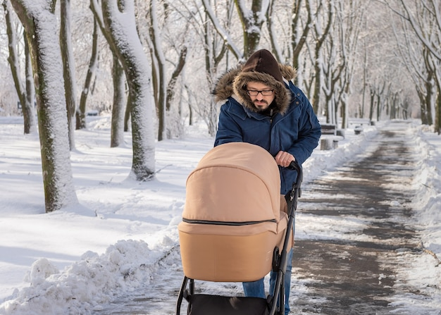 A bearded dad walking with baby carriage in winter park. a man with a baby stroller walks in a winter snow-covered city park in the cold. caring father admires baby sleeping in stroller.
