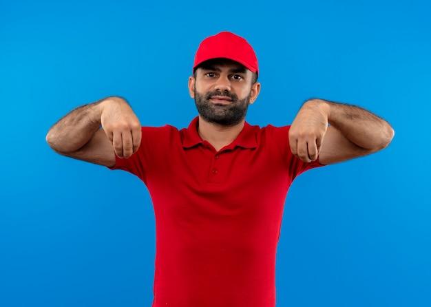 青い壁の上に立っている自信を持って、ボディーランゲージの概念を探している手で身振りで示す赤い制服と帽子のひげを生やした配達人