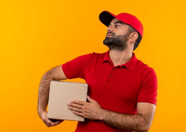 オレンジ色の壁の上に立っている深刻な顔で脇を見て赤い制服とキャップ保持ボックスパッケージのひげを生やした配達人