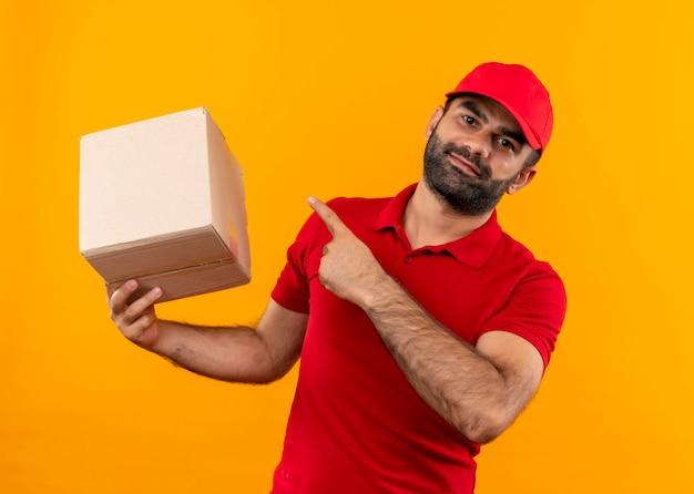 赤い制服を着たひげを生やした配達人とオレンジ色の壁の上に立って自信を持って笑ってそれに指で指しているボックスパッケージを保持しているキャップ