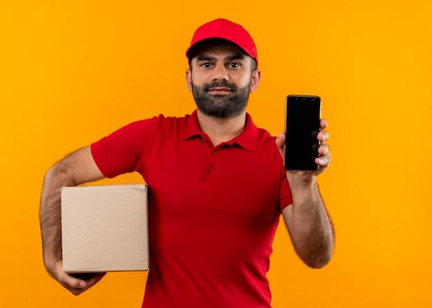 オレンジ色の壁の上に立って自信を持って見えるスマートフォンを示す赤い制服とキャップ保持ボックスパッケージのひげを生やした配達人