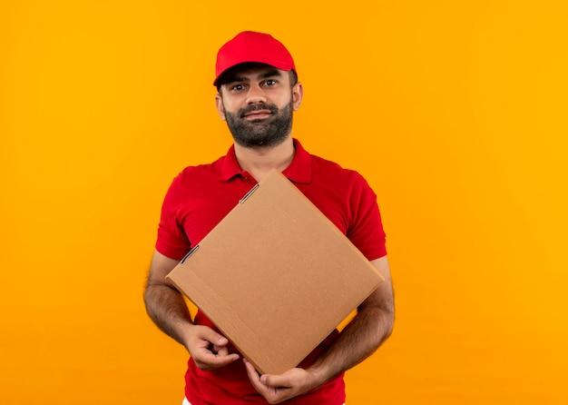 オレンジ色の壁の上に立っている顔に笑顔でボックスパッケージを保持している赤い制服と帽子のひげを生やした配達人