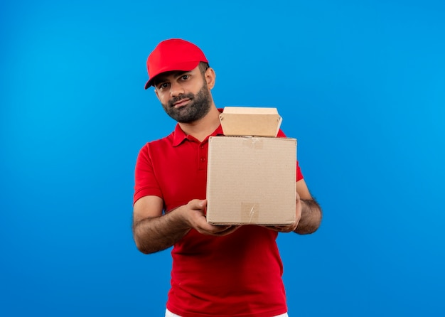 파란색 벽 위에 서있는 얼굴에 미소로 옆으로 찾고 골판지 상자를 들고 빨간 유니폼과 모자 수염 배달 남자