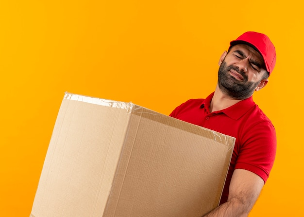 オレンジ色の壁の上に立っている重い重量に苦しんでいる大きな箱のパッケージを保持している赤い制服と帽子のひげを生やした配達人