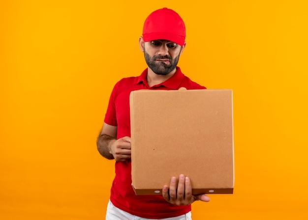 オレンジ色の壁の上に立っている混乱した表情でそれを見て開いているピザの箱を保持している赤い制服と帽子のひげを生やした配達人