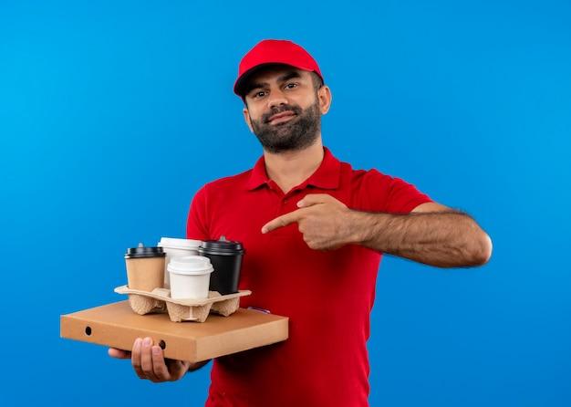 Бородатый курьер в красной форме и кепке держит коробку для пиццы и кофейные чашки, указывая пальцем на них, уверенно улыбаясь, стоя у синей стены