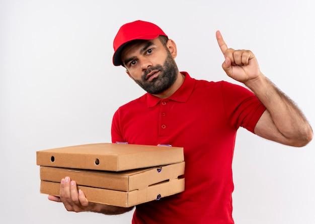 Бородатый курьер в красной форме и кепке держит коробки с пиццей, указывая вверх указательным пальцем, уверенно глядя, стоит над белой стеной