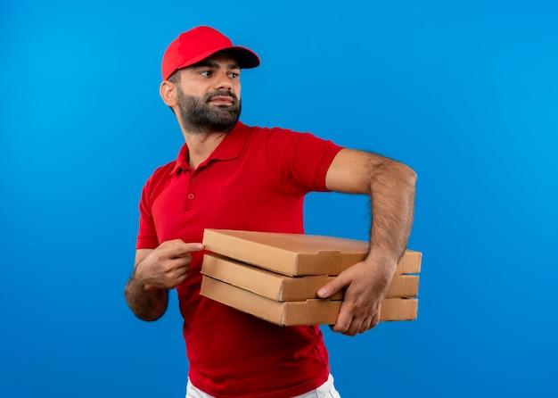 Бородатый доставщик в красной форме и кепке, держащий стопку коробок для пиццы, смотрит в сторону, указывая пальцем на коробки, стоящие над синей стеной