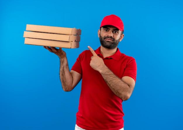 Бородатый курьер в красной форме и кепке держит стопку коробок из-под пиццы, указывая пальцем на них, уверенно улыбаясь, стоя над синей стеной