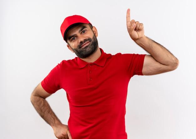 Бородатый курьер в красной форме и кепке, указывая вверх с дружелюбно улыбаясь указательным пальцем, стоя над белой стеной