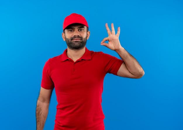 赤い制服を着たひげを生やした配達人と青い壁の上に立っているokサインを示す自信を持って笑顔